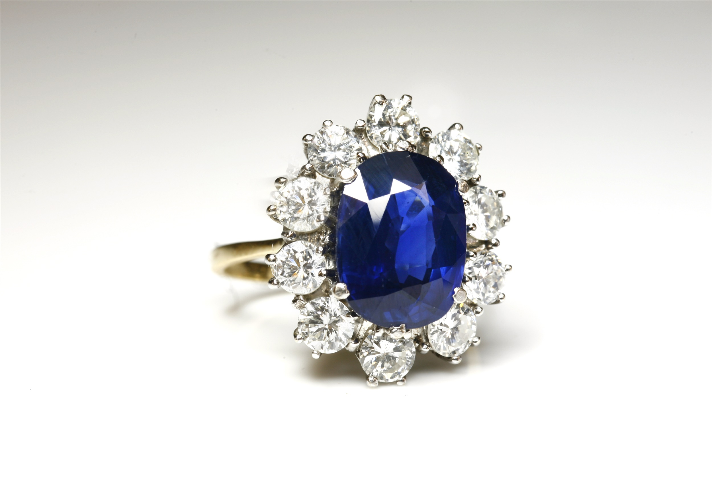 An 18ct gold, sapphire and diamond oval cluster ring