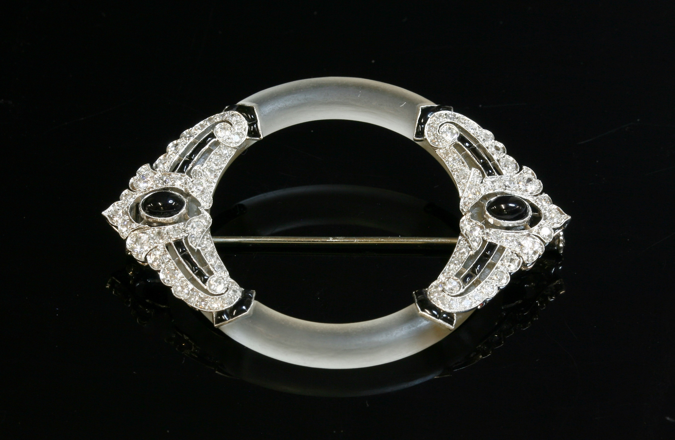 A French Art Deco platinum, gold, rock crystal, onyx and diamond brooch, c.1925