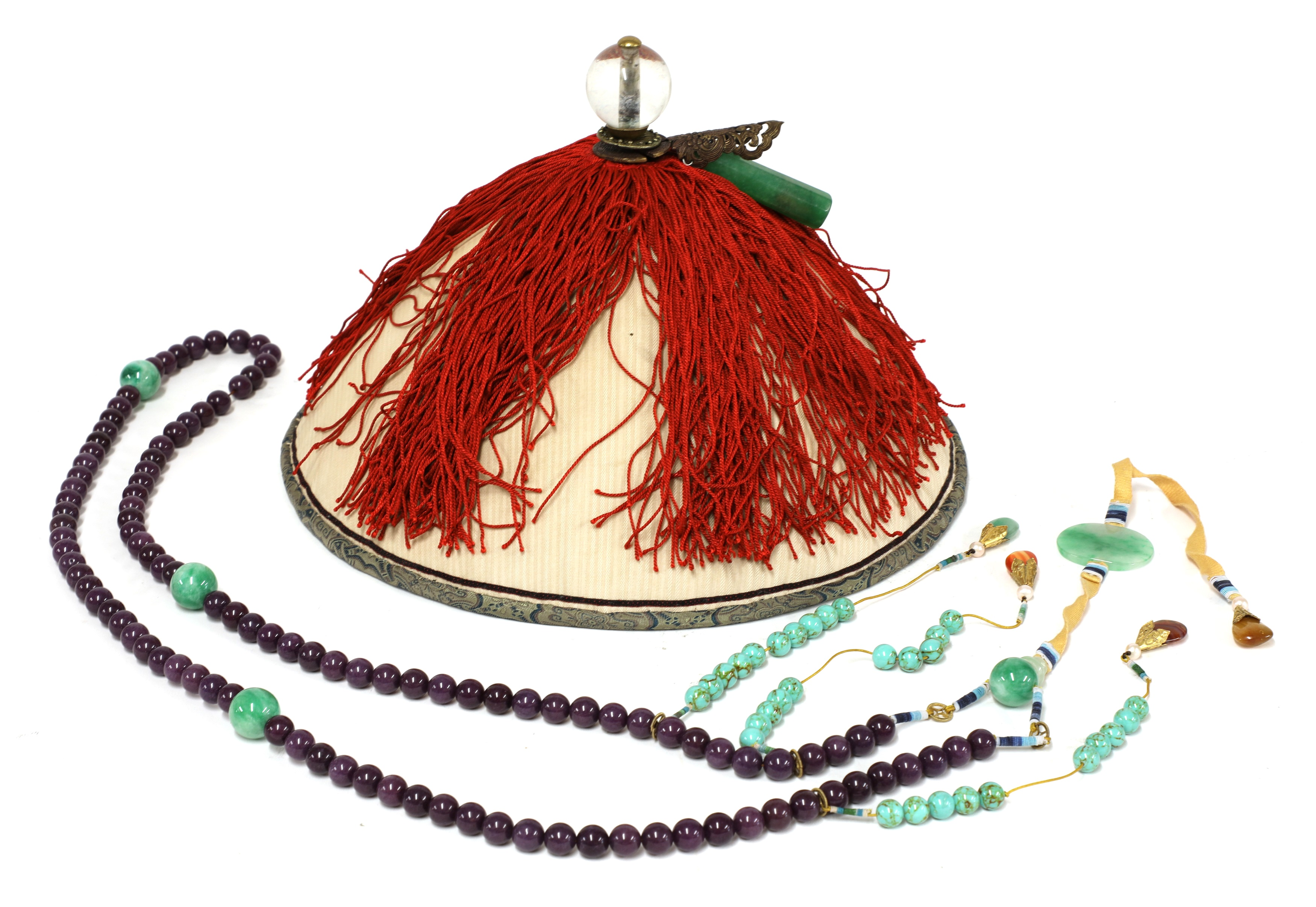 A Chinese official's hat, with a glass ball finial and a jade tube ornament, above red tassels covering the circular domed top, 32.5cm diameter, and a beaded chaozhu