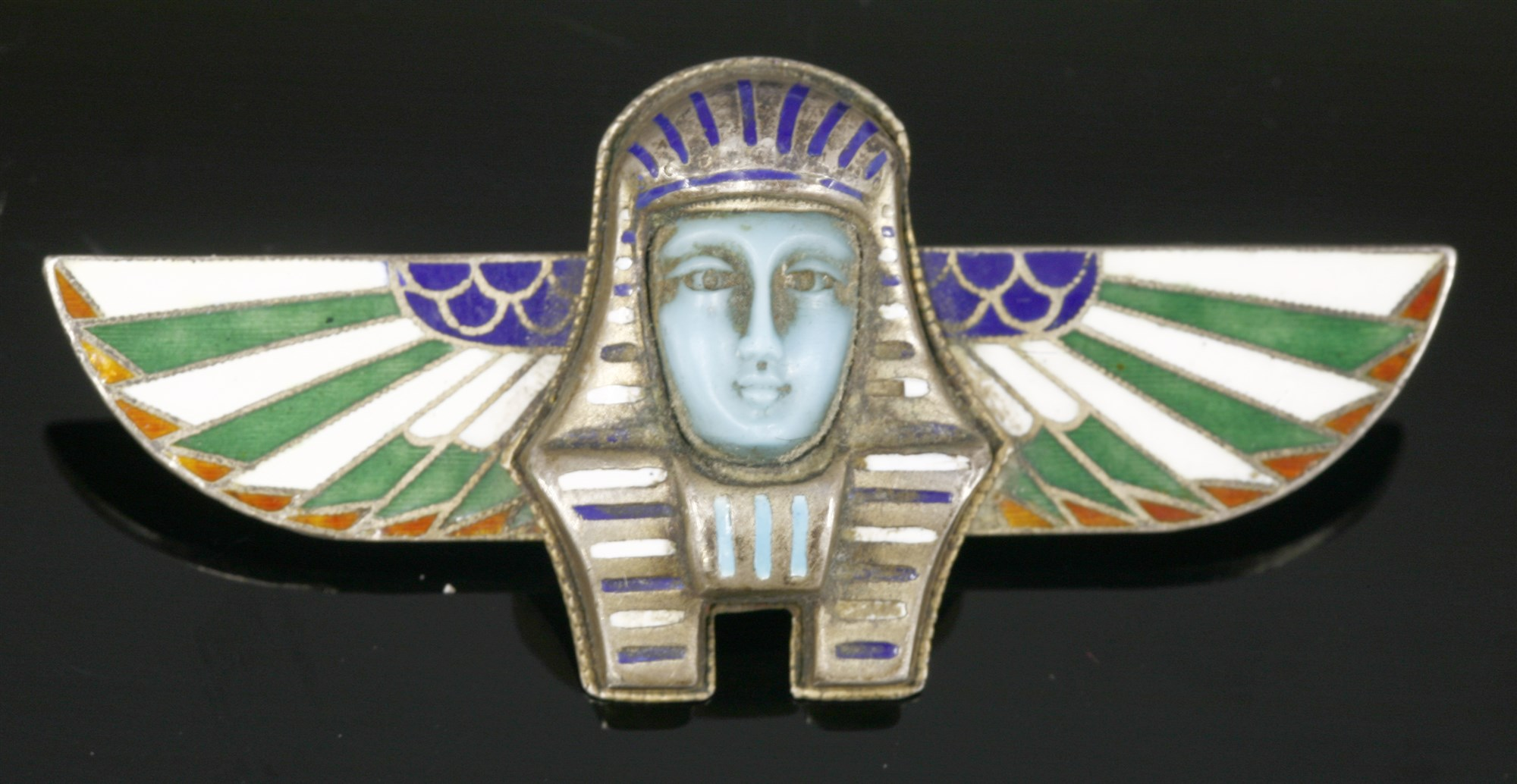 An Egyptian Revival silver and champlevé enamel brooch, in the form of a ba-bird. The ba is an aspect of a person's non-physical being, or 'soul', and could travel out of the tomb after death. The ba was usually represented as a bird with the head of a human, and sometimes with human arms. Silver gilt enamelled pieces of this sort are typical of the Art Deco Egyptian Revival, usually Continental in make (either French or German), and often set with marcasite.  Lot 10, 20th Century Decorative Art & Design Sale, 13th October 2015 Hammer £75