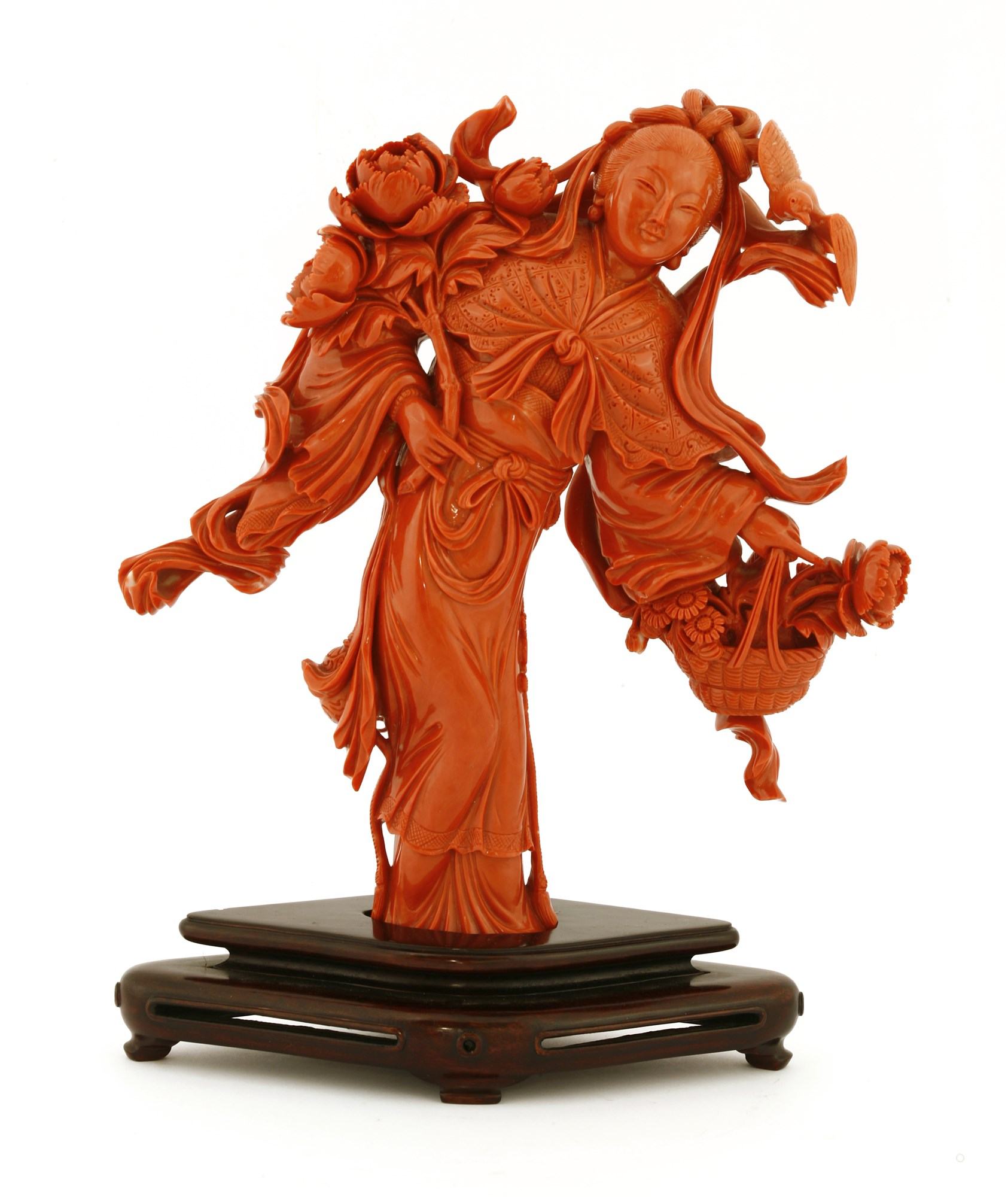 A 20th century coral figure of a lady holding a basket of flowers