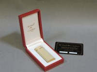 Lot 76 - A Cartier oval ivory coloured lacquer lighter