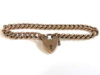 Lot 60 - A gold hollow curb link bracelet with padlock