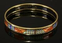 1003 - An Hermès narrow orange enamel gold-plated bangle