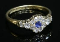 Lot 52 - An 18ct gold sapphire and diamond cluster ring with diamond set shoulders