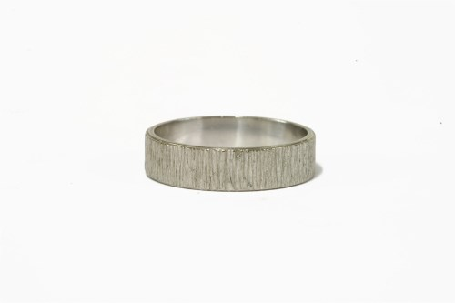 Lot 21-An 18ct white gold bark textured wedding ring
