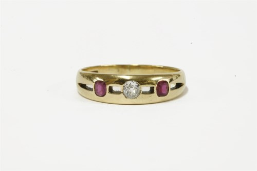 Lot 3-A gold three stone diamond and ruby pierced ring