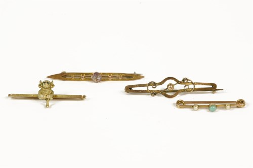 Lot 1008-Four assorted bar brooches to include a 9ct gold devil with rose cut diamond eyes bar brooch