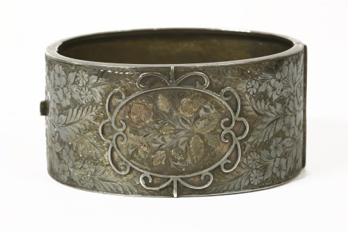 Lot 1022-A Victorian silver hinge bangle with floral scrolling decoration on top section