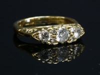 Lot 70-An 18ct gold three stone diamond carved head-style ring