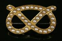 Lot 95 - A gold split pearl overhand knot brooch