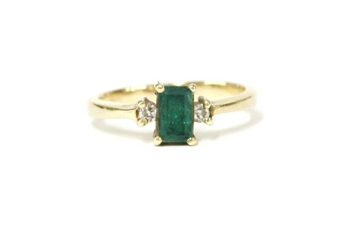 Lot 25-An emerald and diamond three stone ring