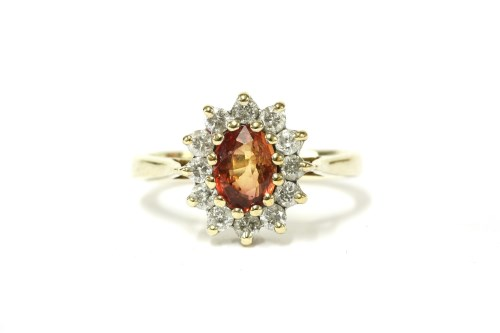 Lot 23-A 9ct gold orange sapphire and diamond cluster ring