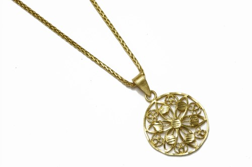 Lot 8-A high carat gold open work floral circular pendant