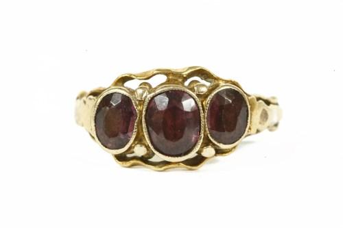 Lot 25-A gold three stone garnet ring