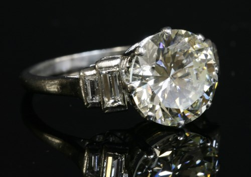 155 - A single stone diamond ring with stepped baguette cut diamond shoulders