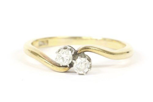 Lot 10-A gold two stone diamond crossover ring