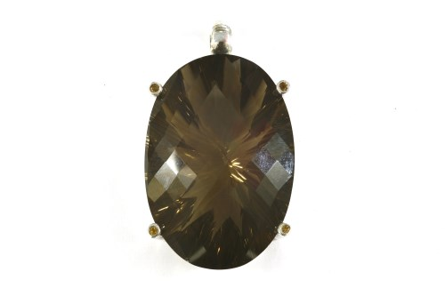 Lot 3-A large silver oval chequer cut smokey quartz pendant