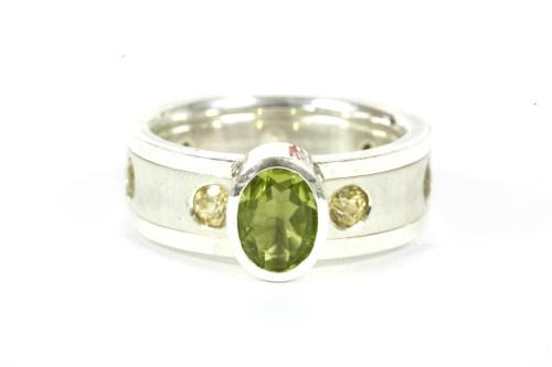 Lot 9-A silver single stone oval mixed cut peridot ring