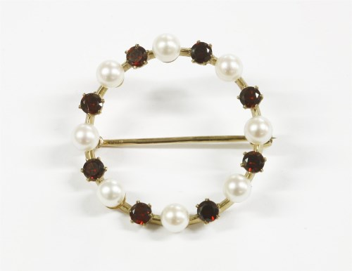 Lot 7-A 9ct gold garnet and cultured pearl circular brooch