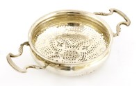 Lot 154 - A George II silver two-handled lemon strainer