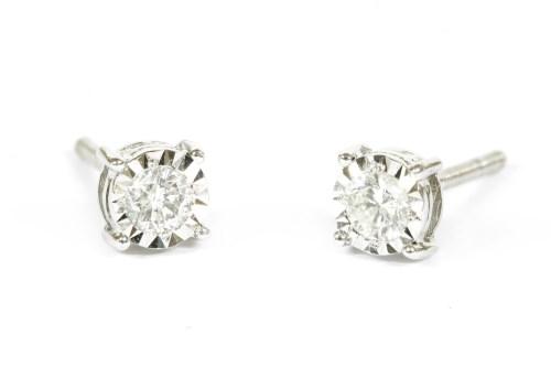 Lot 12-A pair of white gold single stone diamond illusion set earrings