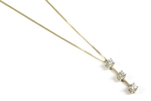 Lot 21-A gold three stone diamond bar pendant