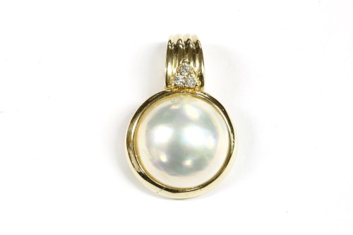 Lot 14-A gold coloured mabé pearl and diamond set three stone cluster ring