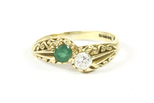 Lot 6-An 18ct gold emerald and diamond crossover ring