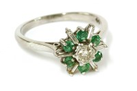 Lot 24-An 18ct white gold diamond and emerald star burst cluster ring