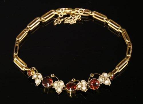Lot 11-An Edwardian garnet and split pearl bracelet