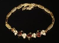 Lot 11 - An Edwardian garnet and split pearl bracelet