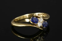 Lot 6-An Edwardian 18ct gold four stone diamond and sapphire crossover ring