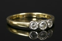 Lot 25-An 18ct gold three stone diamond ring