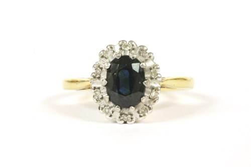Lot 58-An 18ct gold oval cut sapphire and diamond cluster ring