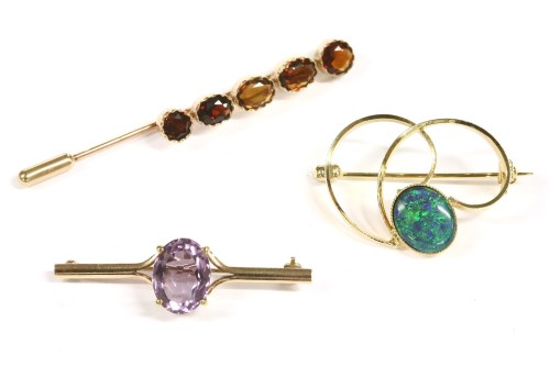 Lot 10-A gold single stone oval cut amethyst bar brooch