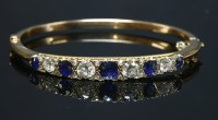 Lot 42-An Edwardian sapphire and diamond hinged bangle