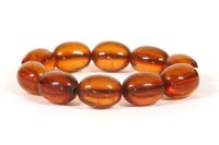 Lot 17 - An early 20th century single row amber olive shaped bead bracelet