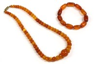 Lot 58-An Art Deco single row graduated half bead shaped amber bead necklace