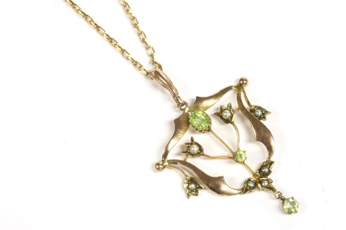 Lot 14-An Edwardian gold peridot and split pearl open frame pendant