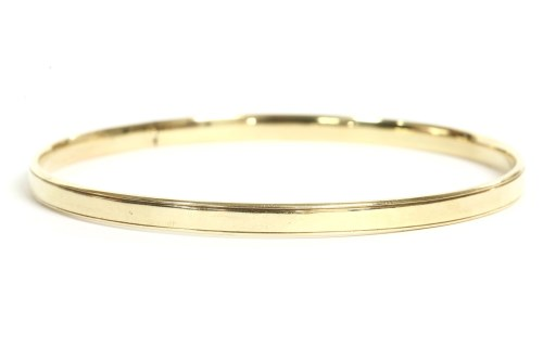 Lot 28-A 9ct gold solid flat section slave bangle