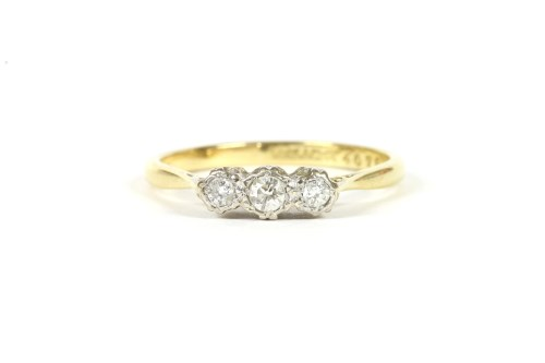Lot 15-A gold three stone illusion set diamond ring