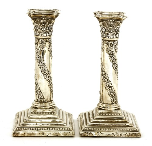 Lot 53-A pair of Edwardian silver candlesticks