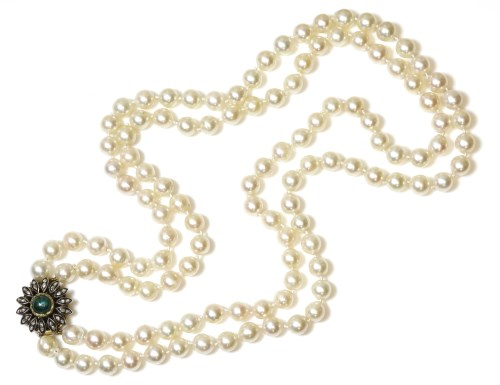 Lot 36 - A two row uniform cultured pearl necklace with an emerald cabochon and diamond floral cluster clasp