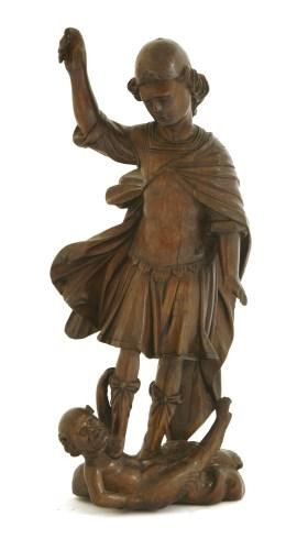 Lot 521-A walnut carving of Saint Michael battling Satan