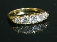 Lot 59-An Edwardian five stone diamond carved head ring