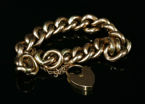 Lot 11-A 9ct gold hollow textured and polished curb link bracelet with padlock
