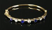 Lot 58-An Edwardian sapphire and diamond hollow hinged bangle