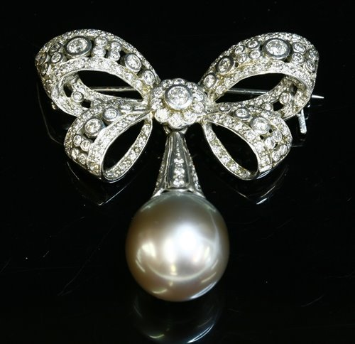 Lot 334 - A white gold Tahitian cultured pearl and diamond bow brooch