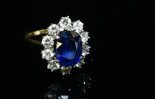 Lot 542-An 18ct gold sapphire and diamond oval cluster ring